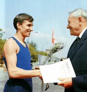 Honoured master of sports, presents his prize to a relay race winner