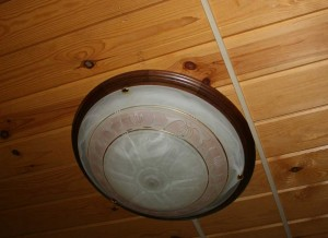 Round lamp with brown piping on the wood-paneled ceiling.