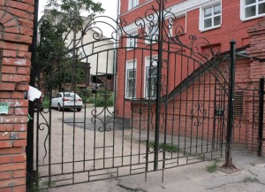 Gates organically look at red-brick building.