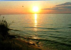 Den Sonnenuntergang über dem Wasser.