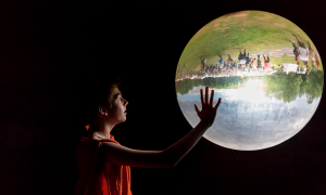 A boy looks at a glass bowl showing the outside upside down in a museum in Bramsche-Kalkriese