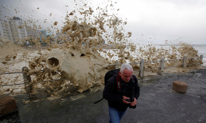 A man runs from sea spray as storms hit Cape Town