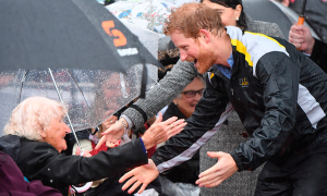 Britain's Prince Harry reacts as he recognises 97-year-old Daphne Dunne, who he had met on an earlier visit to Sydney, during a walk around as it rains at The Rocks in Sydney, Australi