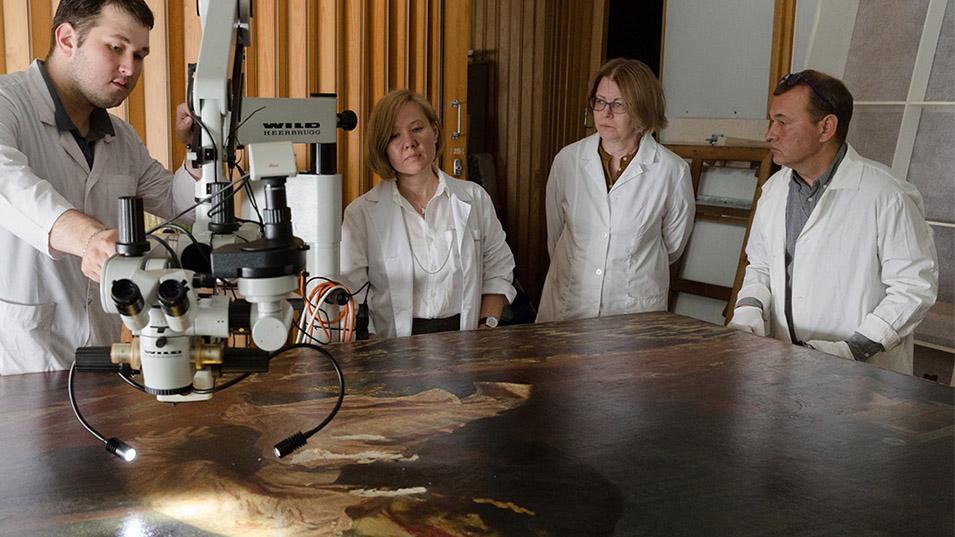 Restorers examining the canvas